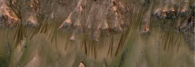 """The dark streaks seen running down these Martian hillsides are examples of """"recurring slope lineae,"""" thought to be evidence of liquid water flows."""