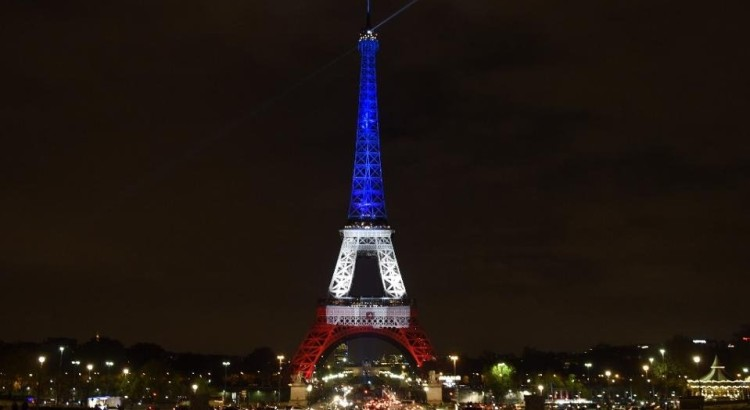 A photo taken on November 16, 2015 in Paris shows the Eiffel Tower illuminated with the colors of the French flag in tribute to the victims of the November 13, 2015 Paris attacks (AFP Photo/Alain Jocard)